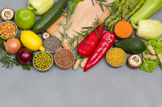 Gesundes lebensmittelkonzept, grüne gemüsesamen-nüsse, hühnerfleisch auf grauem hintergrund
