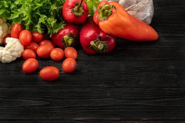 Gesundes lebensmittelkonzept mit gemüse auf dunklem holzhintergrund mit draufsicht und kopienraum