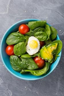 Gesundes lebensmittelkonzept. salat in der blauen schüssel auf dunklem hintergrund.