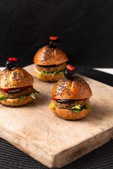 Gesundes lebensmittelkonzept selbst gemachte minihamburger auf hölzernem brett