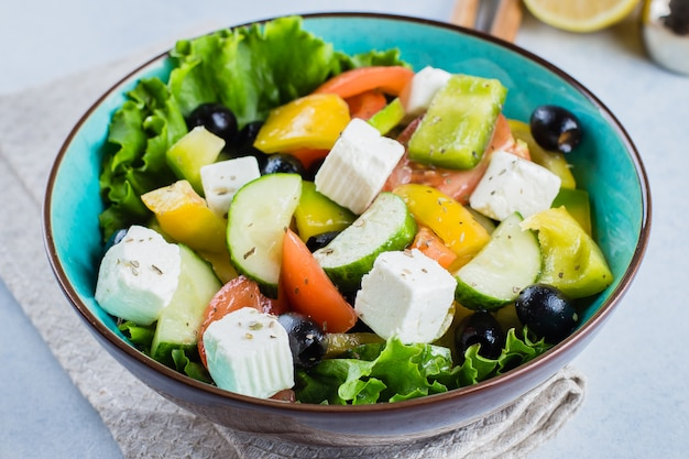 Gesundes lebensmittelkonzept traditioneller griechischer salat mit frischgemüse, feta und schwarzen oliven