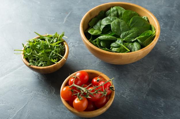 Gesundes lebensmittelkonzept. zutaten für salat. spinat in schüssel, rucola, tomaten.
