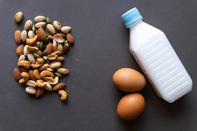 Gesundes lebensmittelkonzeptbild, natürliches lebensmittel von nüssen, milch und gekochten eiern