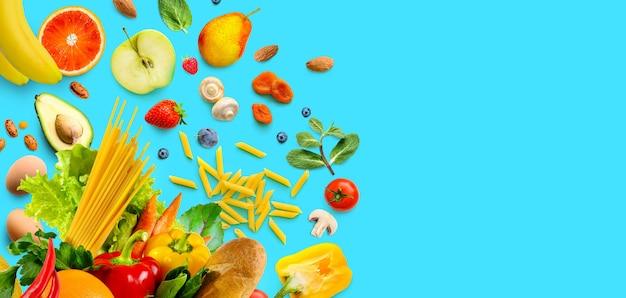 Gesundes lebensmittelsortiment. gemüse und obst, lebensmittel auf aquablauem hintergrund. platz kopieren