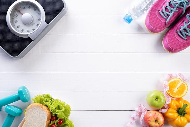 Gesundes lebensstil-, lebensmittel- und sportkonzept auf weißem hölzernem.