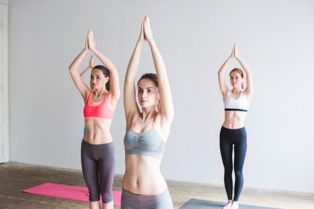 Gesundes lebensstilkonzept der gruppe von frauen, die yoga im fitnessstudio praktizieren