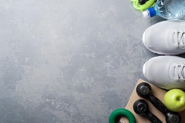 Gesundes lebensstilkonzept. gesundheitstagebuch. turnschuhe, wasser, hanteln mit einem grünen apfel auf einem grauen hintergrund mit kopienraum.