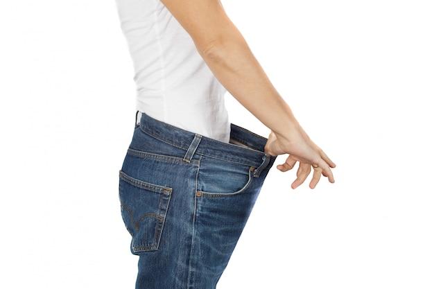 Gesundes lebensstilkonzept gewichtsverlustfrau mit altem jeansgesundheitswesen-, -diät- und -eignungskonzept