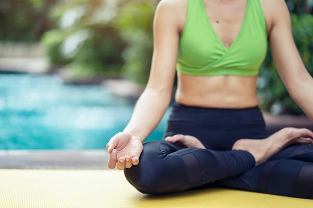 Gesundes lebensstilkonzept. übende yogahaltung der frau meditiert im lotussitz