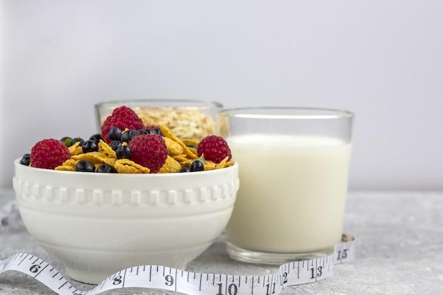 Gesundes leckeres frühstück mit cornflakes und beeren, ein glas milch und ein glas haferflocken.