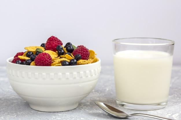 Gesundes leckeres frühstück: schüssel mit cornflakes und beeren und glas milch.