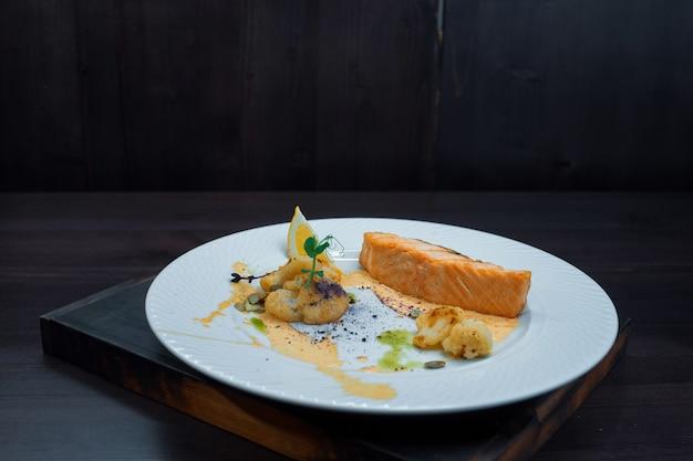 Gesundes leckeres gebackenes lachsfilet mit kürbiskernen mit gebackenem blumenkohl und soße auf einem weißen teller in einem restaurant