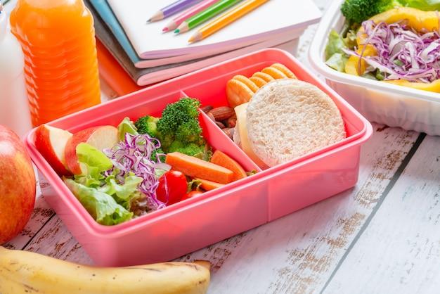 Gesundes lunchbox-set aus sandwichkäse mit cracker und salat in box, banane und apfel, orangensaft und milch.