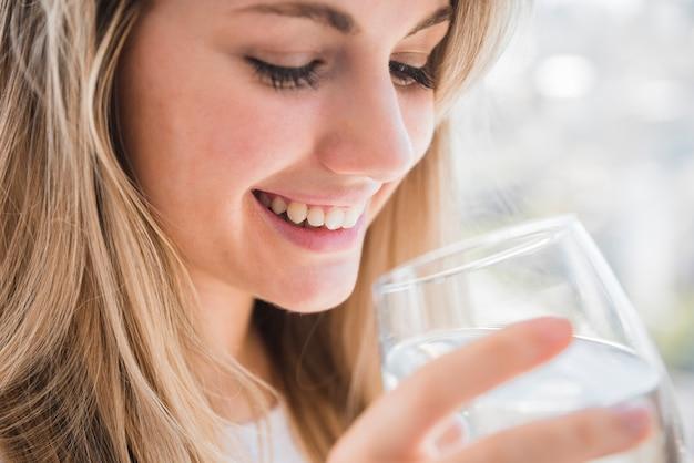 Gesundes mädchen, das glas wasser hält