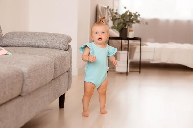 Gesundes mädchen in einem raum neben einem grauen sofa lernt laufen