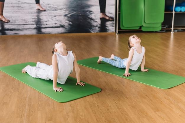 Gesundes mädchen zwei, das auf grüner matte über hölzernem schreibtisch trainiert