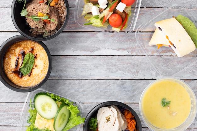 Gesundes mittagessen am arbeitsplatz. fertiggerichte zum essen in lebensmittelboxen, frühstück und mittagessen. nehmen sie mahlzeiten in schwarzen behältern mit besteck auf grauem tisch mit