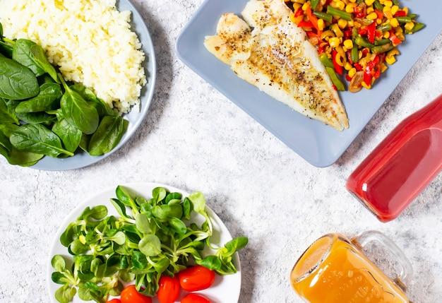 Gesundes mittagessen. das konzept der gesunden ernährung. gebackener fisch, reis, frischer spinat, salat, kirschtomaten, gebackenes frisches gemüse