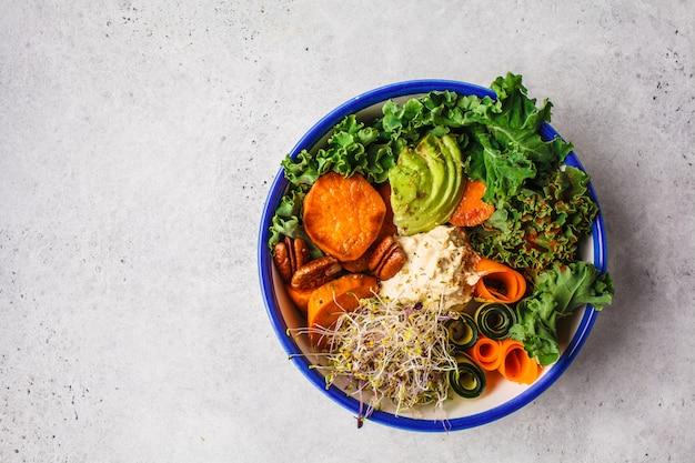 Gesundes mittagessen des strengen vegetariers in der weißen schüssel. buddha-schüssel mit avocados, süßkartoffeln, sprösslingen und gemüse.