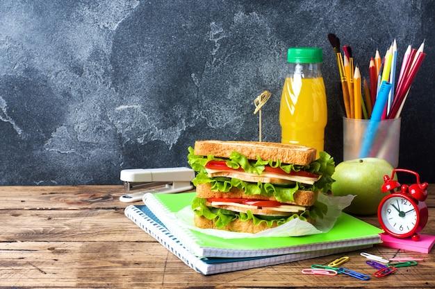 Gesundes mittagessen für die schule mit sandwich, frischem apfel und orangensaft.