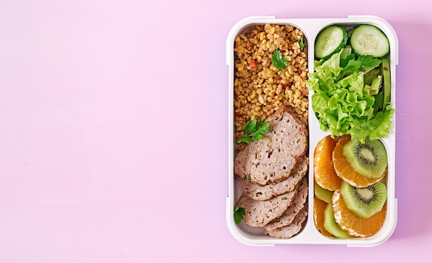 Gesundes mittagessen mit bulgur, fleisch und frischgemüse und frucht auf einer rosa tabelle. eignung und gesundes lebensstilkonzept. brotdose. ansicht von oben