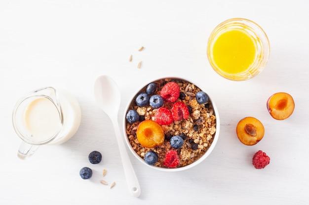 Gesundes müsli zum frühstück mit beerenfrucht, veganer milch