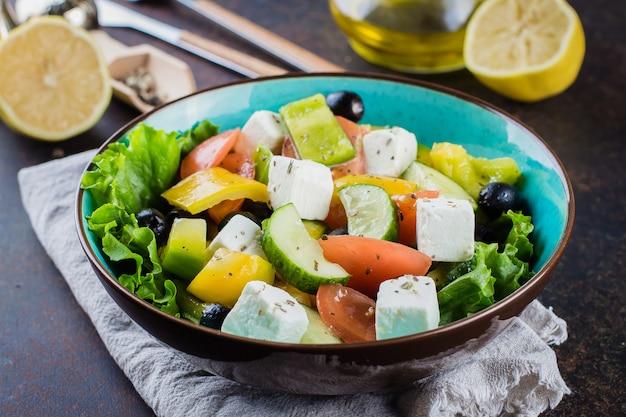 Gesundes nahrungsmittelimbiss-konzept. traditioneller griechischer salat mit frischem gemüse, feta und schwarzen oliven