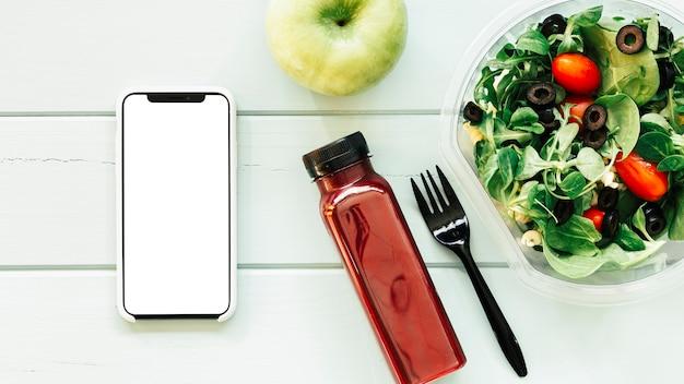 Gesundes nahrungsmittelkonzept mit smartphone nahe bei salat