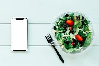 Gesundes Nahrungsmittelkonzept mit Smartphone und Salat