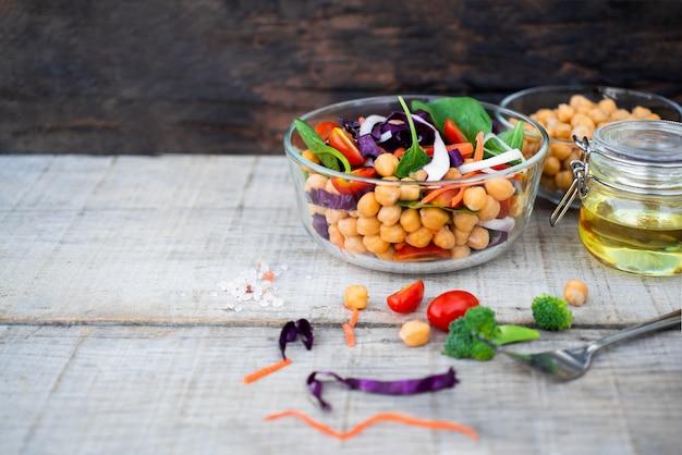 Gesundes nahrungsmittelkonzept, volle schüssel frischer salat spinach, kichererbsen, tomaten,