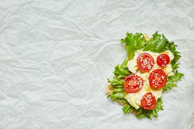Gesundes offenes sandwich mit kopfsalat, tomate lokalisiert auf weißem hintergrund