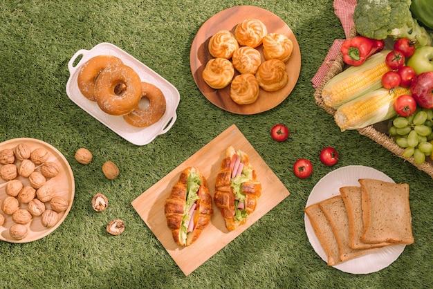 Gesundes picknick für den sommerurlaub mit frisch gebackenen croissants, frischem obst und obstsalat, sandwiches und einem glas erfrischenden orangensaft auf einem rot-weiß karierten tuch und korb