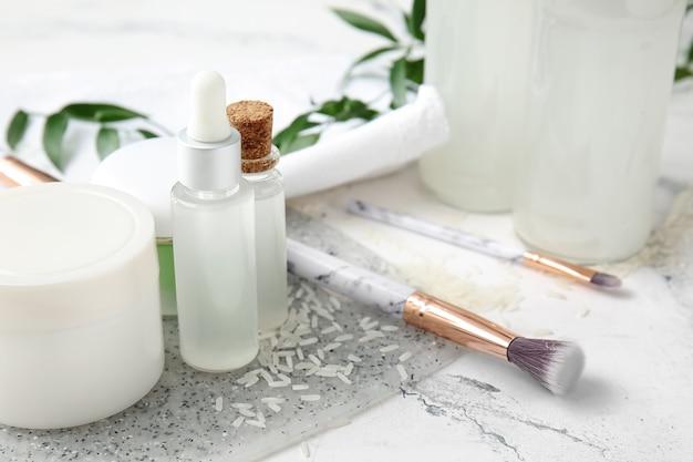 Gesundes reiswasser mit kosmetikartikeln auf weißer oberfläche