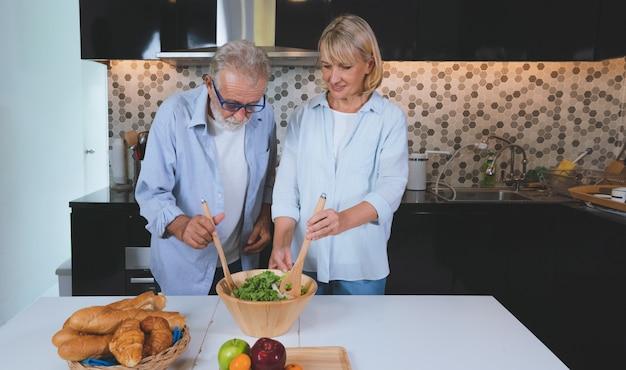 Gesundes salatlebensmittel der glücklichen älteren paare zusammen im küchenraum