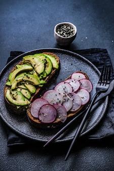 Gesundes sandwich mit avocado und rötlichem gemüse auf betontisch