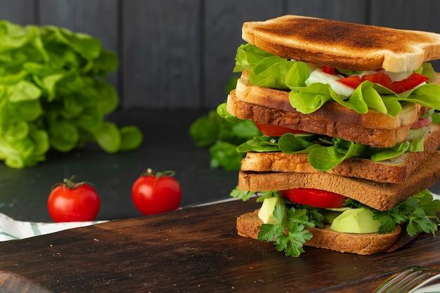 Gesundes sandwich mit gemüse auf dunklem hölzernem hintergrund