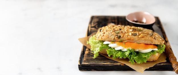 Gesundes sandwich mit lachsen auf weißem hintergrund