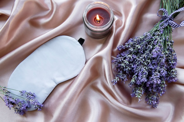Gesundes schlafkonzept. lavendelstrauß, schlafmaske und kerze auf seidenhintergrund