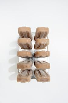 Gesundes schokoladeneis auf einem stock in einer form auf einem weißen hintergrund mit kopienraum. ein köstliches kaltes dessert. flach liegen