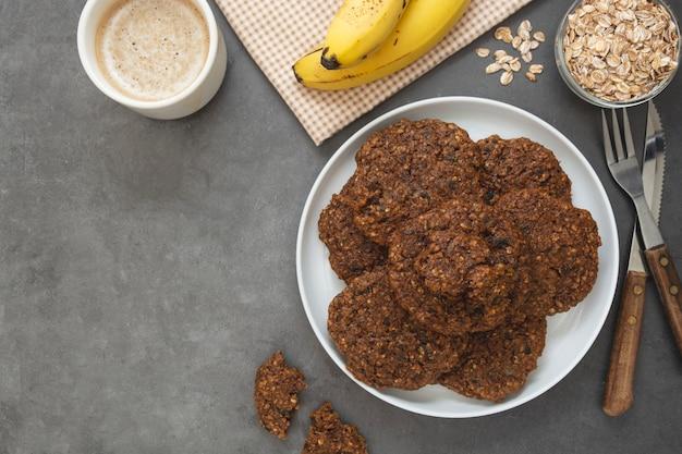Gesundes selbst gemachtes plätzchen mit bananen- und haferflocken, trockenfrüchten und samen.