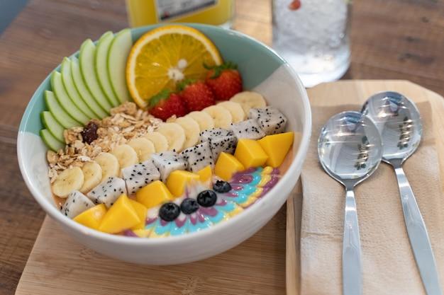 Gesundes smoothie-schüssel-frühstück mit müsli, geschnittener banane, geschnittenen äpfeln, erdbeeren und verschiedenen arten von nüssen