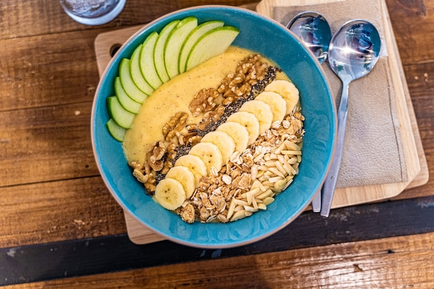 Gesundes smoothie-schüssel-frühstück mit müsli, geschnittener banane, geschnittenen äpfeln und verschiedenen nusssorten