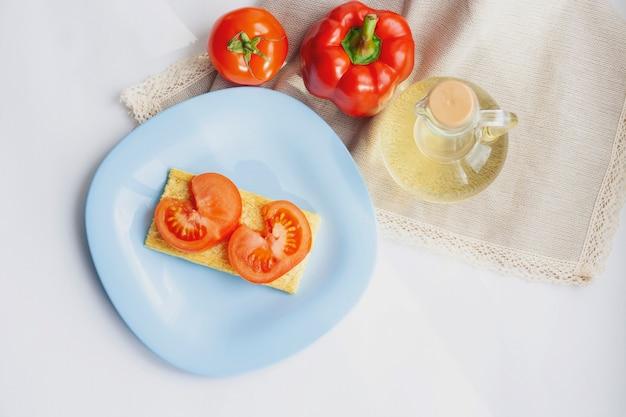 Gesundes snack-gemüsesandwich auf einem blauen teller, tomate, paprika und olivenöl in einer flasche, draufsicht