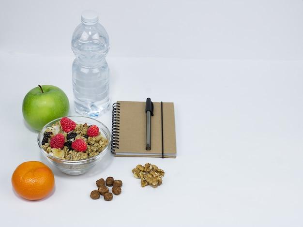 Gesundes snack-müsli-heidelbeer-nusswasser-grüne apfel-notizbücher und stift