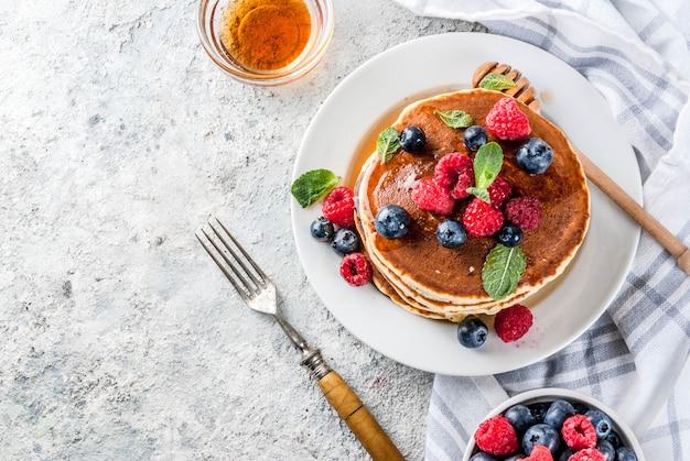 Gesundes sommerfrühstück, selbst gemachte klassische amerikanische pfannkuchen mit frischer beere und honig, draufsicht der hellgrauen steinoberfläche des morgens