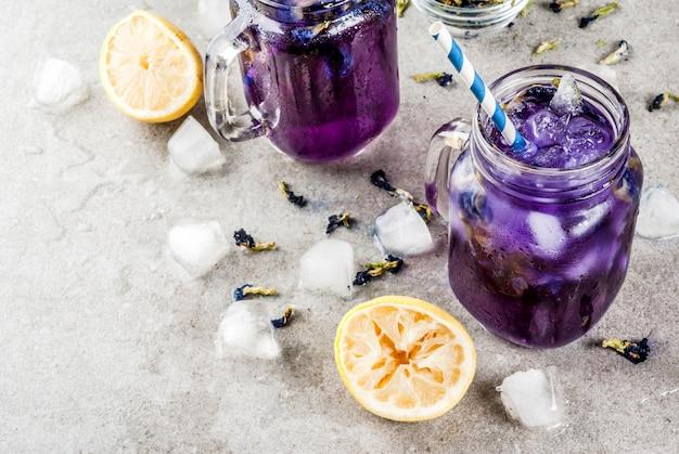 Gesundes sommerkaltgetränk, gefrorener organischer blauer und violetter schmetterlingserbsen-blumentee mit kalken und zitronen
