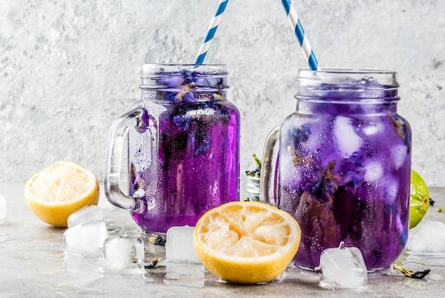Gesundes sommerkaltgetränk, gefrorener organischer blauer und violetter schmetterlingserbsen-blumentee mit kalken