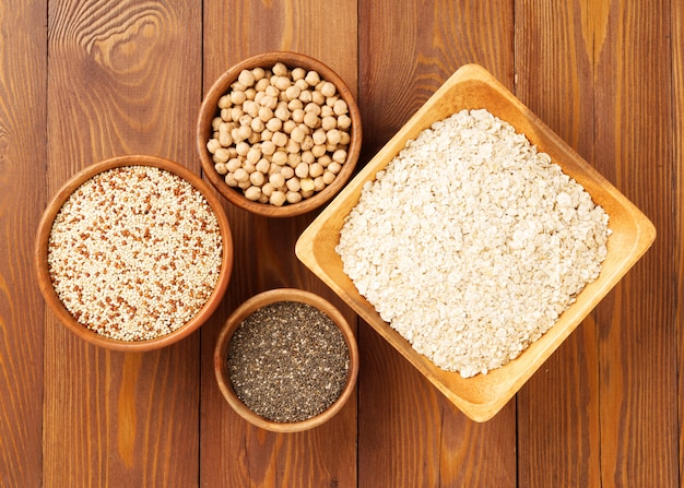 Gesundes superlebensmittel - trockene kichererbsen, quinoa, chia auf braunem hölzernem hintergrund, draufsicht
