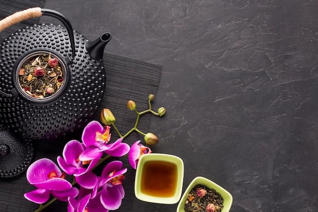 Gesundes trockenes teekraut und schöne rosa orchideenblume auf schwarzem hintergrund