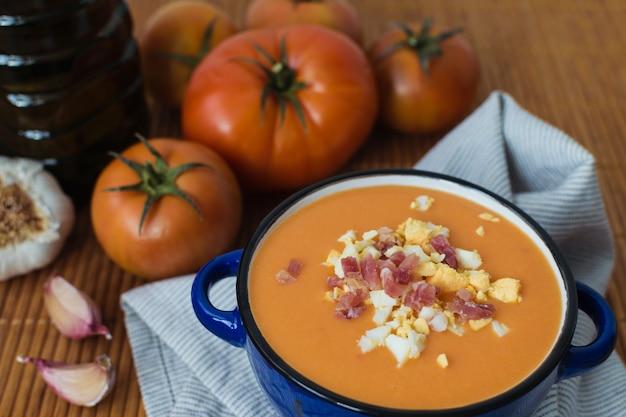 Gesundes typisches spanisches salmorejo in einem topf. tomaten, knoblauch und olivenöl. mediterrane diät hintergrund.